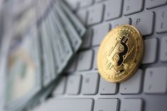 Coin crypto currency bitcoin lies on the keyboard. Background theme gold exchange pyramid for money due to rise or fall exchange rate closeup royalty free stock photography