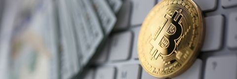 Coin crypto currency bitcoin lies on the keyboard. Background theme gold exchange pyramid for money due to rise or fall exchange rate closeup stock image