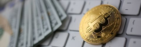 Coin crypto currency bitcoin lies on the keyboard. Background theme gold exchange pyramid for money due to rise or fall exchange rate closeup stock images