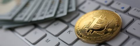 Coin crypto currency bitcoin lies on the keyboard. Background theme gold exchange pyramid for money due to rise or fall exchange rate closeup stock photo