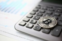 Coin crypto currency bitcoin lies on the keyboard. Coin crypto currency bitcoin lies on calculator keyboard background theme silver exchange pyramid for money royalty free stock photos
