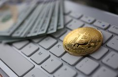 Coin crypto currency bitcoin lies on the keyboard. Background theme gold exchange pyramid for money due to rise or fall exchange rate closeup stock photography