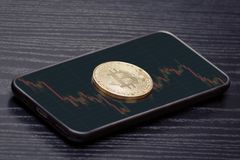 Coin crypto currency Bitcoin on the smart phone with graphic. Bl. Ack wooden table Royalty Free Stock Image