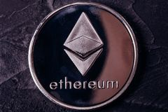 Coin of the Crypto-currency close-up of the Ethereum. Ethereum coin from the metal of a crypto-currency close-up on a dark background royalty free stock photos
