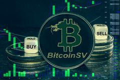 Coin cryptocurrency bsv bitcoin sv stack of coins and dice. Exchange chart to buy, sell, hold. The coin cryptocurrency bitcoin sv bsv stack of coins and dice royalty free stock photo