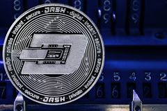 Coin cryptocurrency Dash against the numbers of the arithmometer. Coin cryptocurrency Dash and the numbers of the arithmometer. The concept of production or stock photos