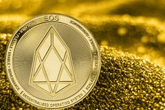 Coin cryptocurrency EOS on golden background. Coin cryptocurrency EOS and gold fabric background royalty free stock image