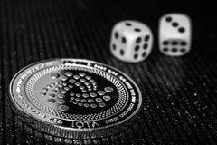Coin cryptocurrency iota and rolling dice. stock photography