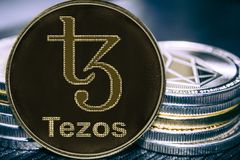 Coin cryptocurrency Tezos XTZ on the background of a stack of coins. MKR stock illustration