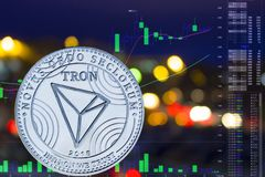 Coin cryptocurrency TRON on night city background and chart. stock illustration