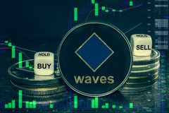 Coin cryptocurrency waves platform stack of coins and dice. Exchange chart to buy, sell, hold. The coin cryptocurrency waves stack of coins and dice. Exchange stock photo