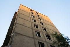 Coin d'un bâtiment à plusiers étages abandonné Fenêtres cassées, bois Photo libre de droits