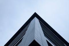 Coin d'un gratte-ciel sous un ciel nuageux et froid vu du fond Photographie stock