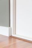 Coin de pièce, porte blanche, plancher en bois, mur gris Photo libre de droits