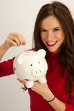Woman makes Coin Deposit into Piggy Bank royalty free stock photo