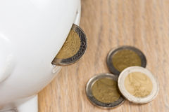 Coin disappearing in a piggy bank. Coin disappearing in a hole: a concept of deposit Royalty Free Stock Images
