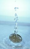 Coin falling in water Royalty Free Stock Photo
