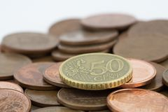 Coin of fifty euro cents on several bronze coins of five cents. White background royalty free stock images