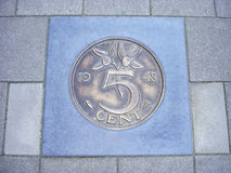 Coin of five cents in pavement Stock Photos