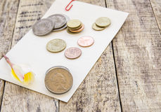 Coin and flower on white paper on wooden table Stock Images