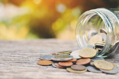 Coin in glass jar on old wood stock photos