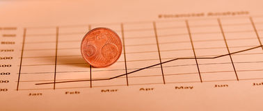 Coin On Graph. Closeup shot euro coin on the growing stock graph Stock Images