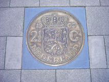 Coin of 2,5 guilders in pavement Stock Image