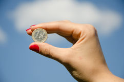 Coin in the hands against the sky. Coin in the hands against the blue sky Stock Image
