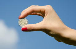 Coin in the hands against the sky. Coin in the hands against the blue sky Royalty Free Stock Photography