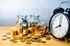 Coin jars and clock. Saving money for retirement royalty free stock photography