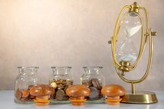 Coin jars and hourglass. Save money for retirement royalty free stock images