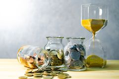 Coin jars and hourglass. Save money for retirement royalty free stock photo