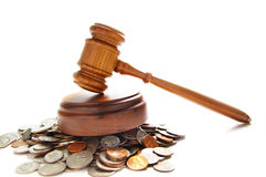 Coin law. Judges law gavel on a pile of coins, over white Royalty Free Stock Image