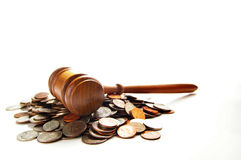 Coin law. Judges law gavel on a pile of coins, over white Stock Photos