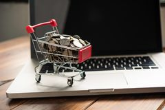 coin in mini shopping cart on table for work and laptop for work royalty free stock images