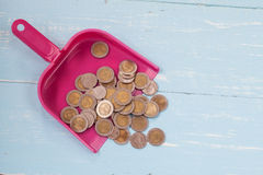 Coin or money in dust pan on wood. Table Stock Photos