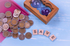 Coin or money in dust pan and wood text. `save ` on Stock Image