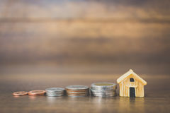 Coin money and house model on wooden background. Finance and banking concept Stock Photo