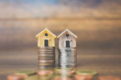 Coin money and house model on wooden background. Finance and banking concept Stock Image
