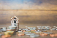 Coin money and house model on wooden background. Finance and banking concept Stock Photos
