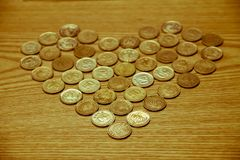 Coin money placed on a wooden table is heart-shaped, love Valentine day. stock images