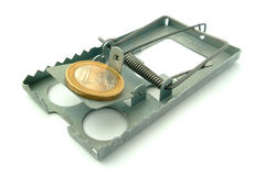 Coin on mousetrap. A steel mousetrap with a Euro coin as bait. Isolated on a white background Stock Photography