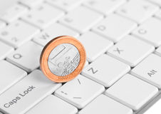 Coin one euro is on the keyboard. Coin one euro is on a the keyboard Stock Photo