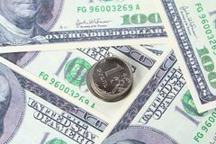 Coin one ruble against the background US dollars background. Coin one ruble against the background US dollars background Stock Image