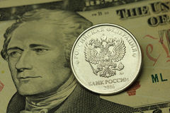 Coin in one Russian ruble against the backdrop of American ten dollar. Background Royalty Free Stock Photos