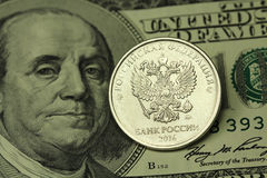Coin in one Russian ruble on a background of American hundred dollar. Background Stock Photos