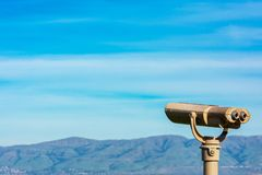 Free Coin Operated Binocular Telescope For Distant Viewing. Blurred Range Of Green Hills, Mountains In The Distance Under Cloud Sky Royalty Free Stock Images - 168344329