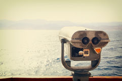 Coin operated binoculars viewer in front of the sea landscape Stock Photos