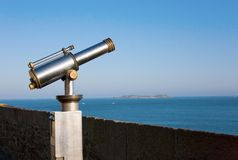 Coin operated viewfinder telescope overlooking sea. Shore Royalty Free Stock Images