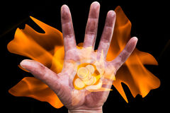 Coin on palm of hand with blaze Stock Photos